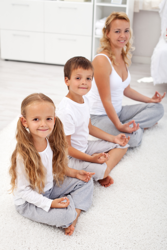 Happy smiling kids doing yoga relaxation at home with their mother - focus on the little girl