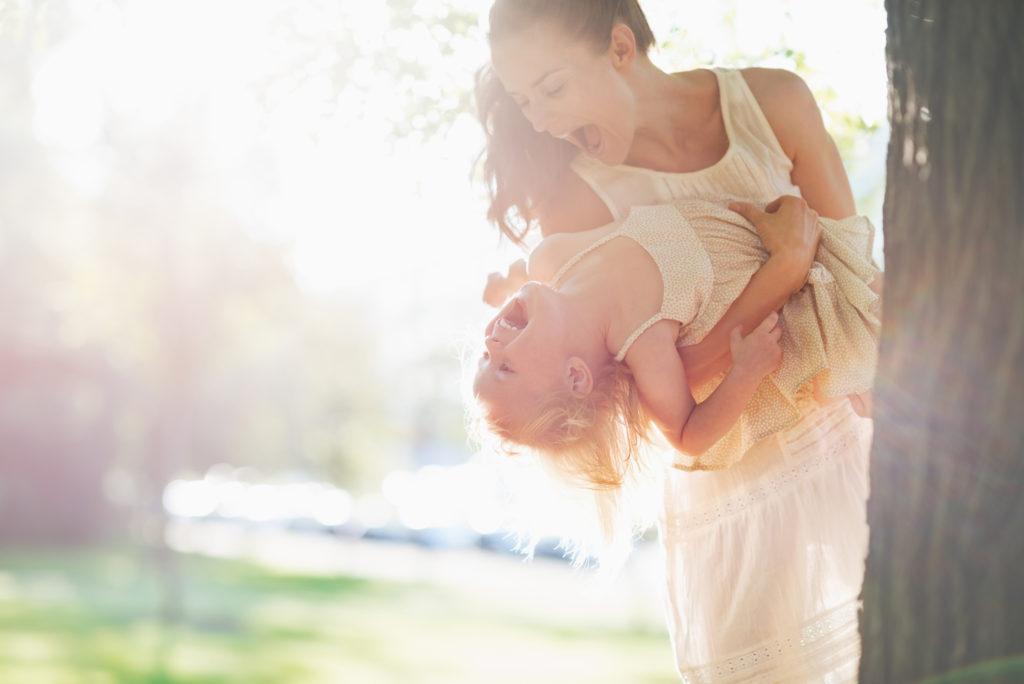 Happy mother and baby having fun near tree